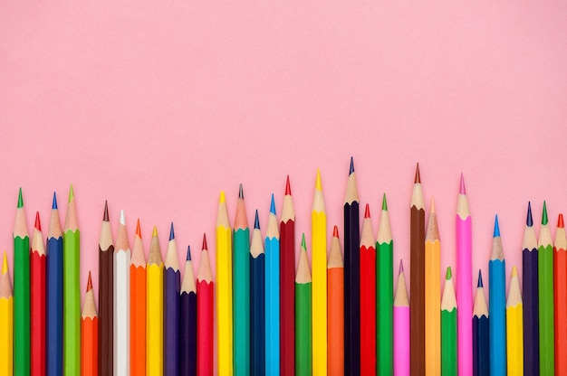 Colored pencils set on pink background