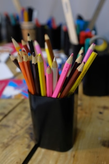 Colored pencils in a stand on a wooden table. school of drawing, children's creativity.