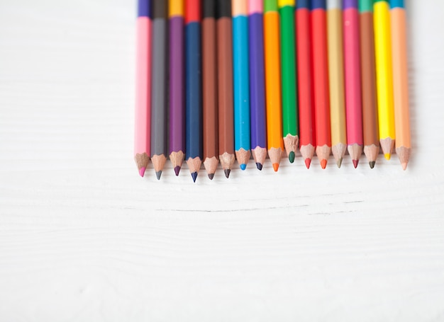 Colored pencils with copy space isolated on white background, education frame concept.