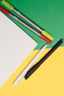 Colored pens and markers on a bright background and a white notepad on the table