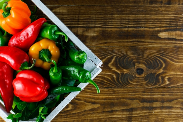 Colored peppers with leaves in a wooden box on wooden surface, flat lay.