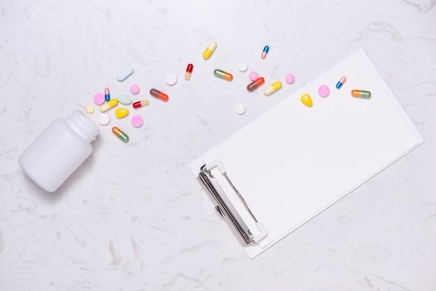 컬러 약과 테이블에 빈 노트북입니다. 플랫 레이.