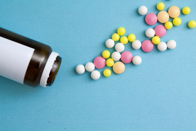 Colored pills are scattered on a blue background. near a glass bottle. treatment, medication, medicine concept.