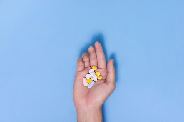 青い背景の手に色の丸薬。