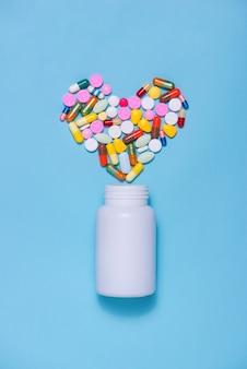 青い背景の上のボトルとハート形の色の丸薬。