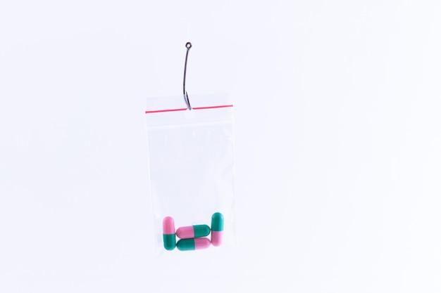 釣り針の小さなジップロックバッグにぶら下がっている色の丸薬や錠剤