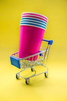 黄色の背景のカートの色のプラスチックカップ