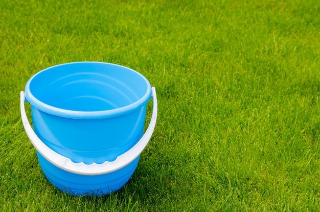 푸른 잔디의 색된 플라스틱 정원 양동이