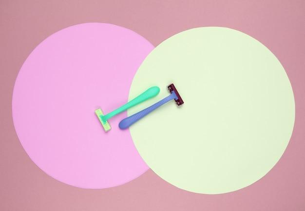 Цветные пластиковые бритвы на фоне розово-желтых пастельных кругов. минималистичный натюрморт красоты