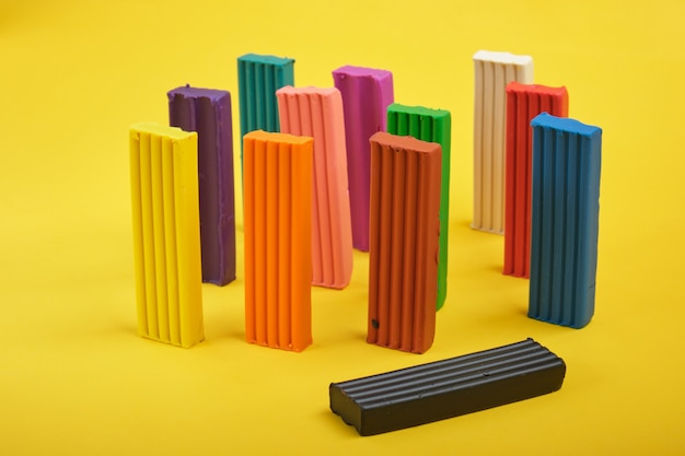Colored plasticine on yellow background copy space