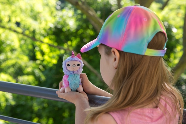 Colored plush llama unicorn in hands little girl with greens