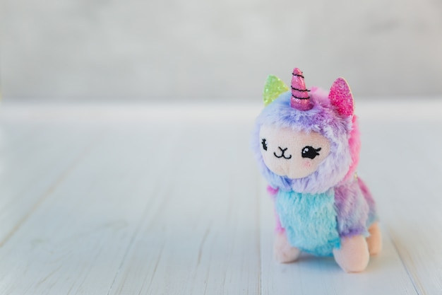 Colored plush llama unicorn on white wood