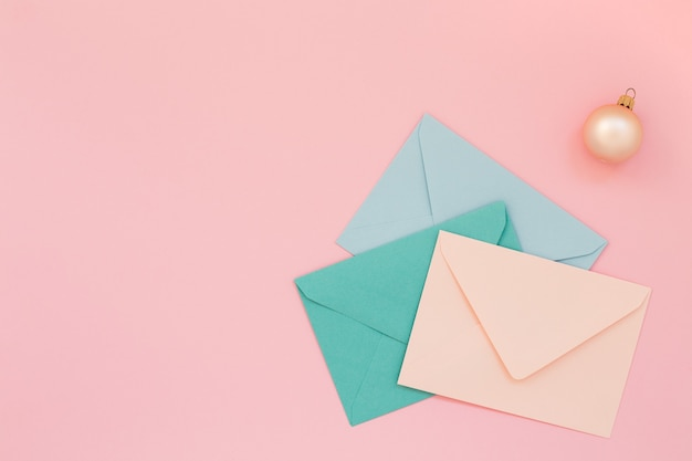 ピンクの背景に色付きの郵便封筒とクリスマスボール、コピースペース。