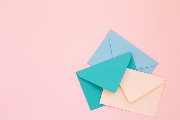 Colored postal envelopes on pink background