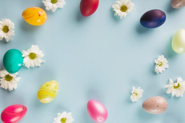 Colored quail eggs near flowers