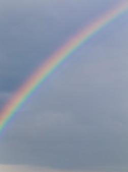 Цветная радуга на фоне пасмурного грозового неба и дождя, пейзаж, небольшая глубина резкости, фото не в фокусе в качестве фона