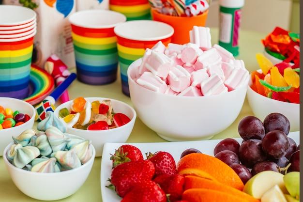 Цветной радужный моноблок, сладости и фрукты ярких цветов на столе