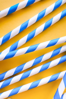 Colored, reusable, striped straws for drinking juice or cocktail on yellow background.