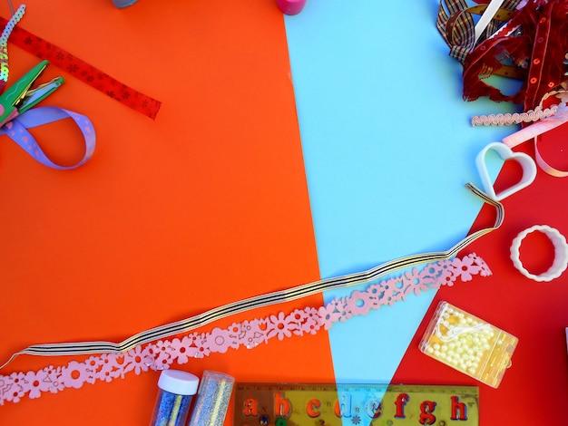 오렌지 배경에 글자와 컬러 리본, 금형, 가위, 자주색과 통치자