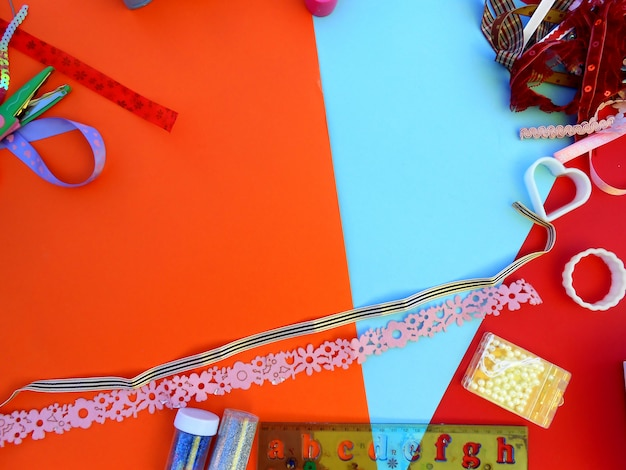 Colored ribbons, molds, scissors, purples and ruler with letters on orange background