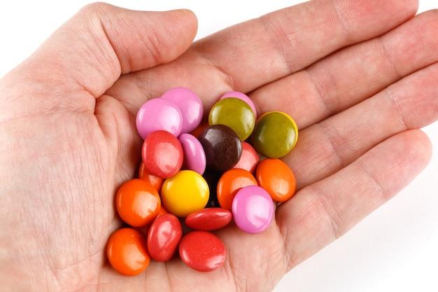 Цветные круглые шоколадные конфеты или жевательная резинка в руке