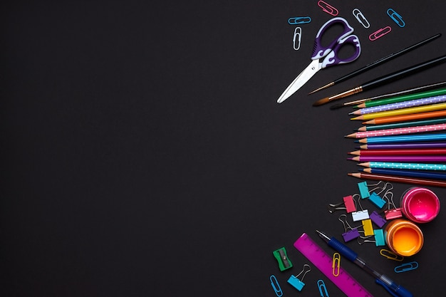 Colored school supplies for learning on black, flat lay