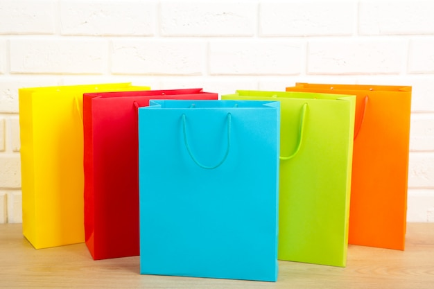Colored shopping bags on a white wall