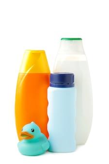 Цветные бутылки геля для душа и утка, изолированные на белой стене. вид сверху