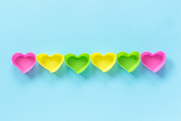 Colored silicone heart shaped molds dish for baking cupcakes lined in row on blue paper background.