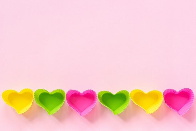 Colored silicone heart shaped molds dish for baking cupcakes lined in row bottom edge on pink paper background.