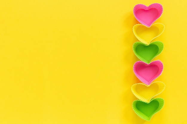 Colored silicone heart shaped molds dish for baking cupcakes lined in row right side on yellow background.