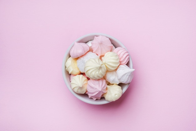 Colored small meringues on pink. flat lay concept. copy space.