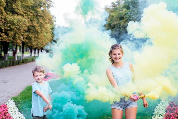 色の煙と子供。明るい緑と黄色のパーティーの煙。誕生日やパーティー。子供たちは楽しく、笑って走ります。幸せな明るい夏。