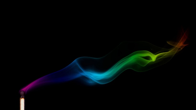 Colored smoke from a put out match isolated on black background