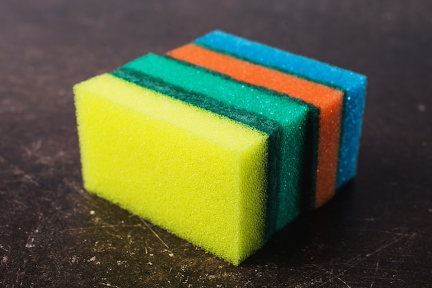 Colored sponges against dark marble background. items for hygiene and washing dishes