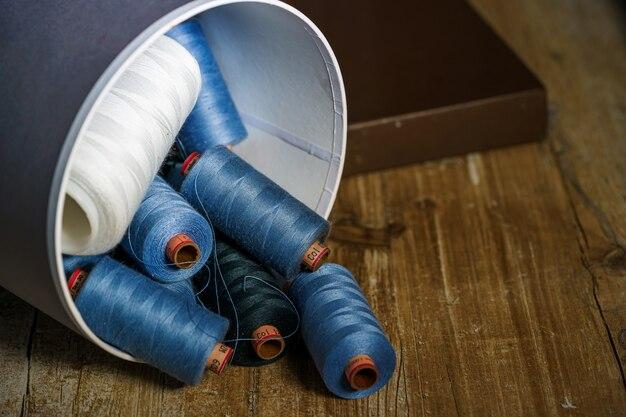 Цветная катушка с нитью выпадает из коробки. деревянный стол. концепция шитья.