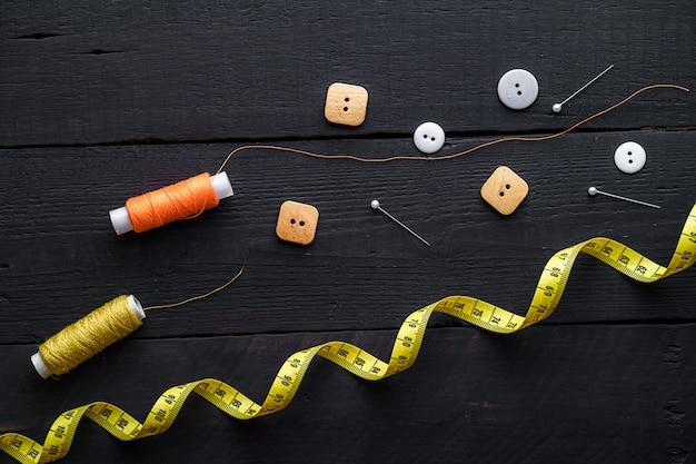 木製の茶色の表面に縫うための色付きの糸、ピン、測定テープ、ボタンのスプール