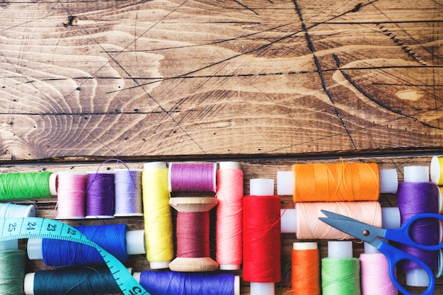Colored spools of thread laid out in rows on wooden background. copy space.