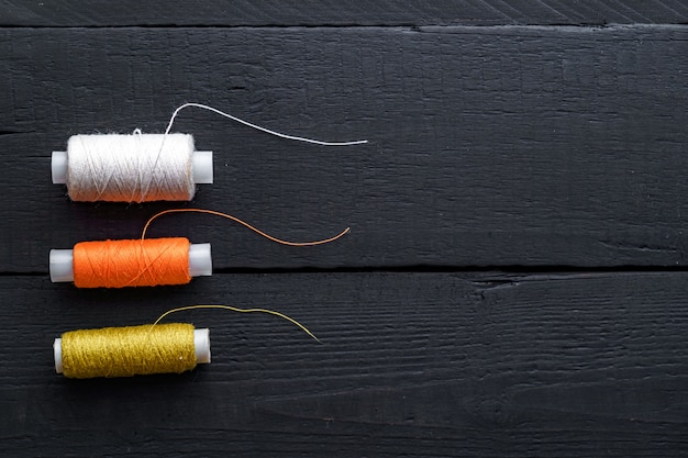 Colored spools of thread for sewing on a wooden black background. copy space