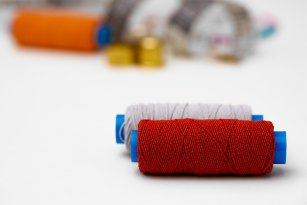 Colored spools of threads on white background