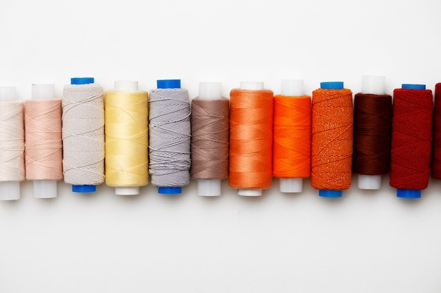 Colored spools of threads on white surface