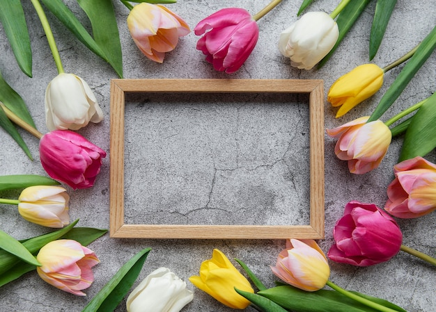 Colored spring tulips and wooden frame on a concrete surface