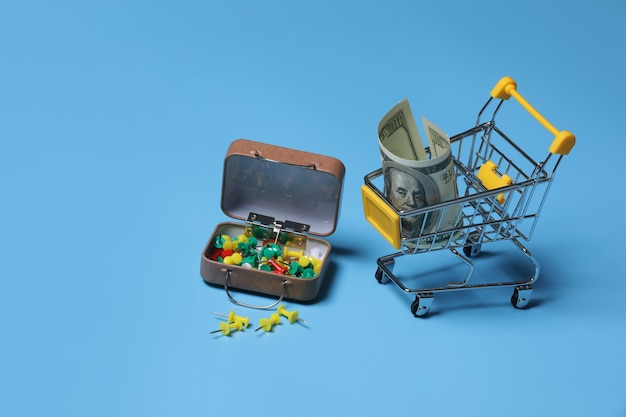 Colored stationery buttons and trolley with money on blue