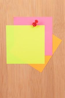 Цветные стикеры, прикрепленные к деревянной доске для сообщений