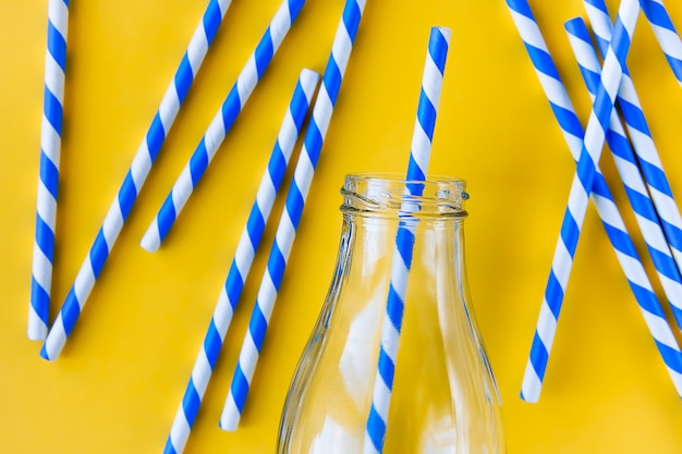 Colored, striped straws for drinking juice or cocktail, in a glass bottle