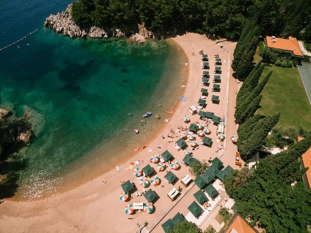 컬러 파라솔은 위에서 przno보기의 왕실 해변 모래 위에 서 있습니다.
