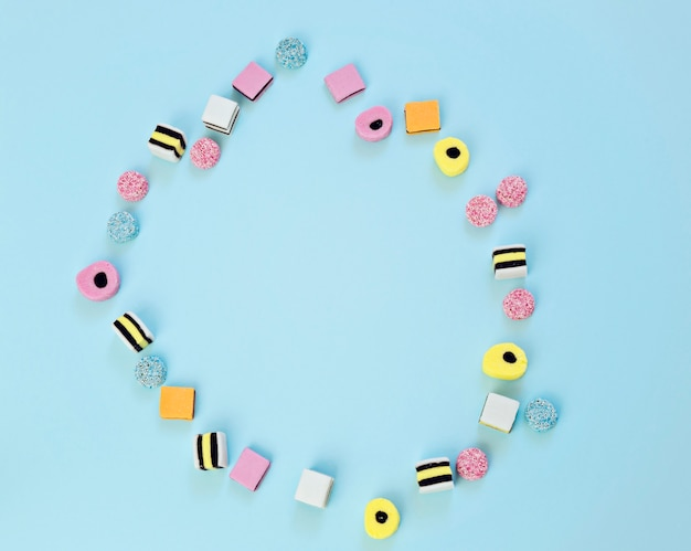 Colored sweets are scattered on a blue background