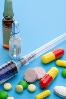 Цветные таблетки, шприц для инъекций и ампулы с препаратом. фармацевтическая индустрия. синий стол,