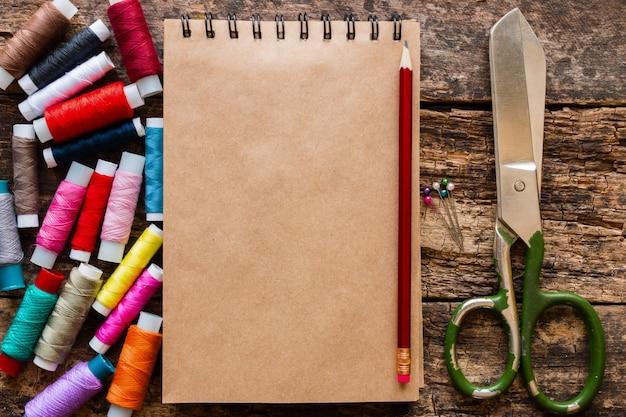 Цветная нить, ножницы и блокнот для заметок на деревянной