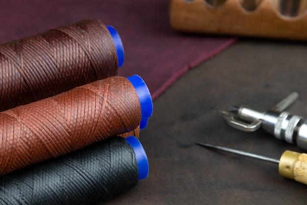 革を縫うための色付きの糸のスプールは、ワークショップのテーブルに置かれます